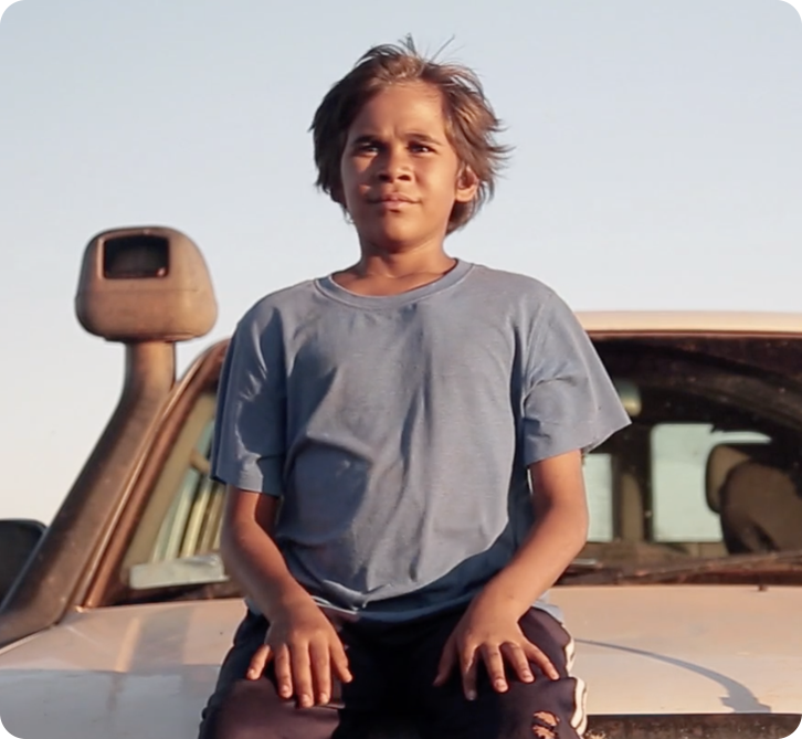Young boy sits on the bonnet of a car looking out into the sunset.